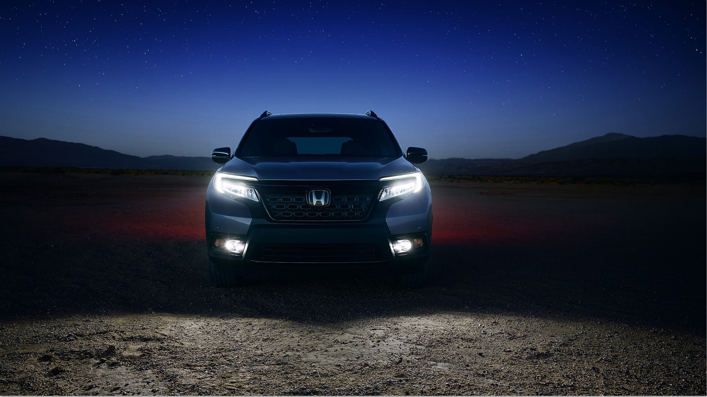 Direct front view of 2020 Honda Passport Elite in Modern Steel Metallic with LED low-beam headlights and fog lights on.