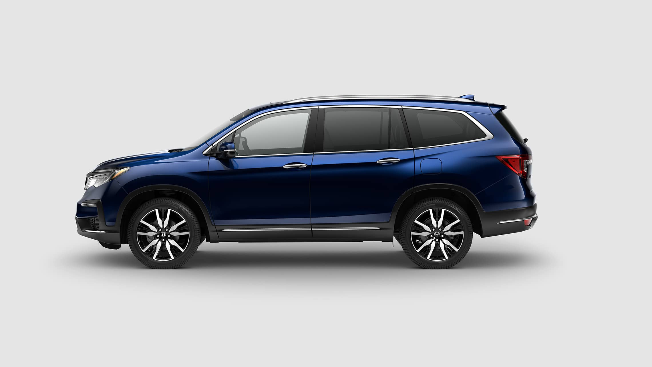 Driver side profile of 2020 Honda Pilot Elite in Steel Sapphire Metallic.